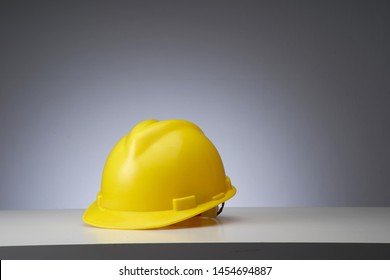 yellow construction hard hat on the gray background