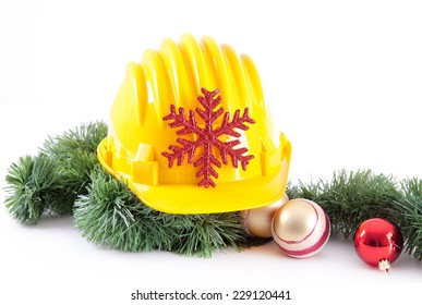 Yellow construction helmet and christmas decoration on white background