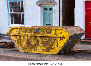 Yellow construction skip on a residential road in England.