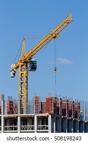 Yellow construction tower crane and house under construction
