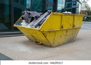 Gelber Behälter mit Bauabfall zur Beseitigung