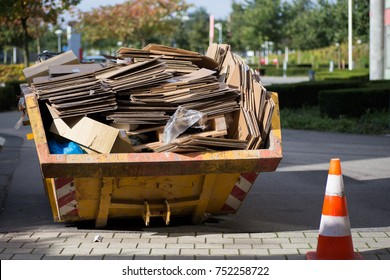 Yellow container with paper waste for disposal.