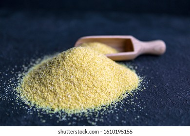 Yellow corn flour with spoon on a dark textured background. Ingredients for preparation of a Italian traditional Polenta, porridge made from cornmeal. Organic food. Selective focus with copy space.