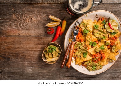 Yellow corn nacho chips garnished with ground beef, guacamole, melted cheese, peppers and parsley leaves in plate with beer on wooden table, top view with copy space