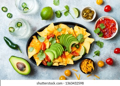Yellow corn nachos chips with melted cheese sauce, avocado, jalapeno, cilantro leaves, tomato salsa and spicy iced margarita cocktail