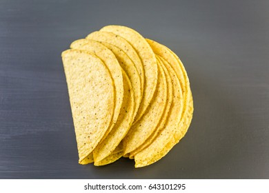 Yellow corn taco shells on a gray background.