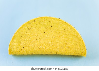 Yellow corn taco shells on a blue background.