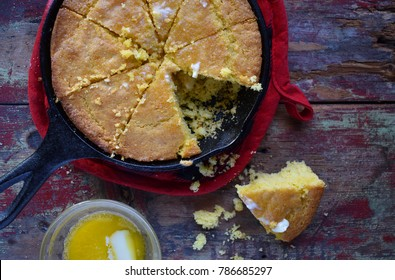 Yellow Cornbread in cast iron skillet on rustic wood table top view
