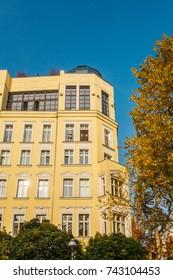 yellow corner building next to an autumn tree