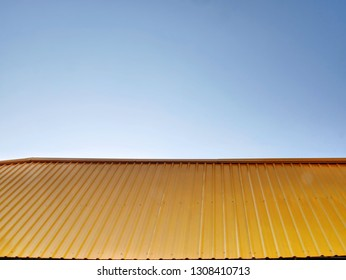 Yellow Corrugated Metal Roof Against Blue Sky