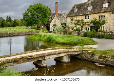 Yellow Cotswold limestone footbridge over the River Eye in Lower Slaughter village in Cheltenham England with The Old Mill museum buildings Lower Slaughter, Cheltenham, England - June 16, 2019