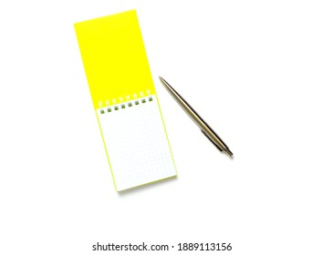 yellow cover notepad with metal pen isolated on white background. flat lay.