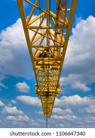 Yellow crane against the clear blue skies with lush clouds.