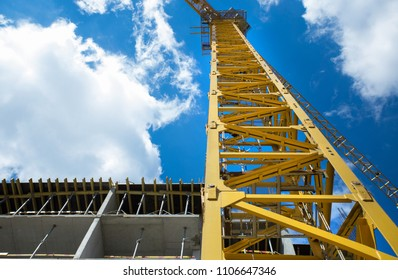 Yellow crane against the clear blue skies with lush clouds. Near the construction site.
