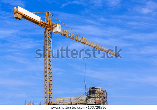 yellow crane against white cloud and blue sky