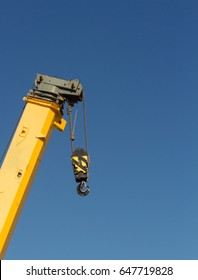 Yellow crane boom with blue sky background
