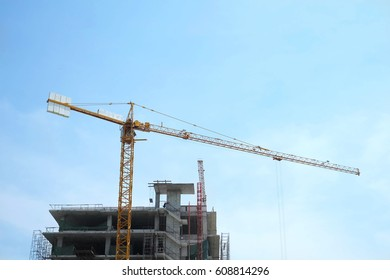Yellow crane and building under construction on blue sky