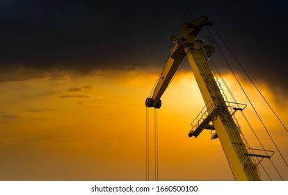 Yellow crane in cargo port translating coal. Industrial scene. Cargo crane at sunset