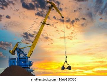 Yellow crane in cargo port translating coal. Industrial scene