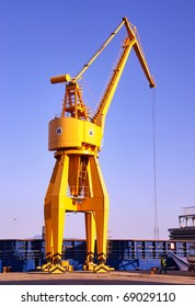 Yellow crane unloading cargo ships in the dock