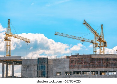 Yellow cranes and building under construction against blue sky.