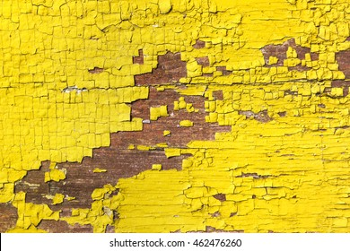 Yellow craquelure of the delaminated paint on wooden background