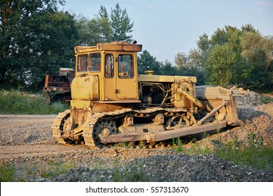 Yellow crawler tractor in  gravel canyon.