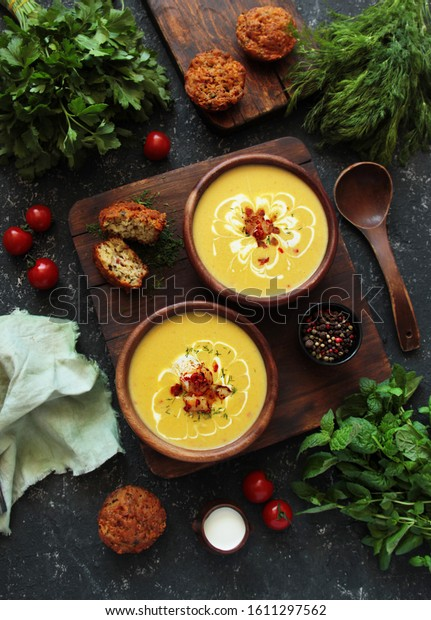 yellow cream soup with scallops and seafood. Sea soup on a dark background