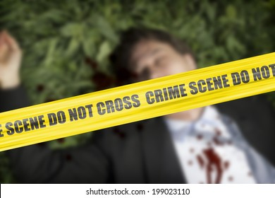 Yellow crime scene cordon tape over a blurred body of a man in the grass, unidentifiable person