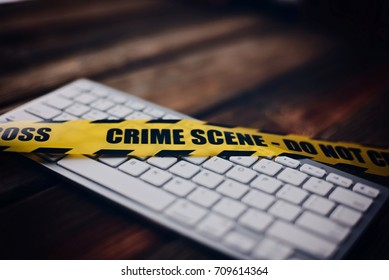 Yellow crime scene tape on computer keyboard. Computer crime concept.