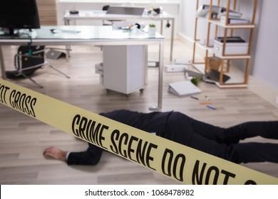 Yellow Crime Scene Tape Over Dead Man's Body Lying On Floor