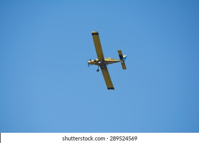 Yellow crop-duster airplane turning around in flight to fly back over the field and spray the next sector of the crop.  Blue sky background.  The Mississippi agricultural industry.