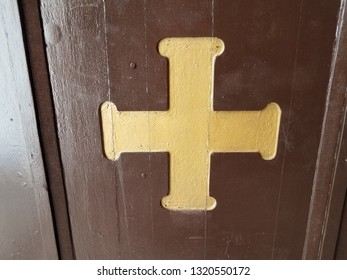 yellow cross symbol on brown wood surface