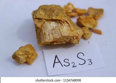 Yellow crystal of the mineral auripigment, or arsenic sulfide, with its chemical formula.