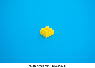 yellow cubic plastic block on blue paper background . object in the middle and many space for text . isometric business concept .