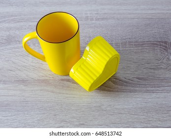 Yellow cup and heart shaped plastic box placed on a wooden table