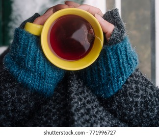 Yellow cup of tea at the female hands