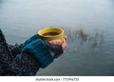 Yellow cup of tea at the female hands by the river in the winter