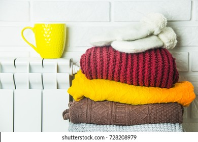 yellow cup of tea on a white battery next to a pile of warm winter sweaters