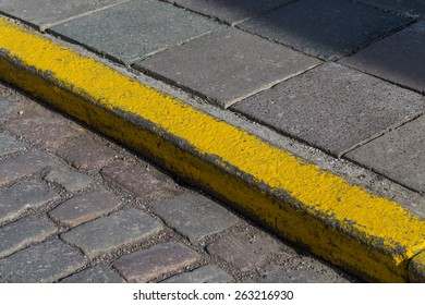 Yellow curb stone border in an old town road