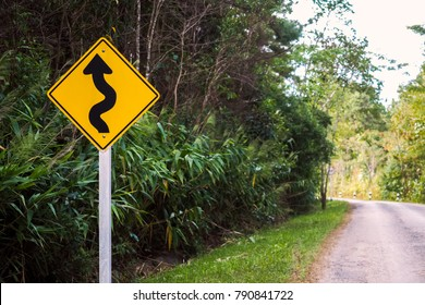 Yellow curvy road sign to the mountain in rural area steet