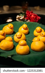 Yellow cute duck shaped Baozi chinese steamed bun on lotus leaf in restaurant