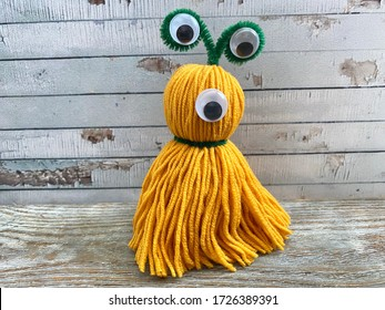yellow, cute monster with one eye, children's craft, made of wool yarn.