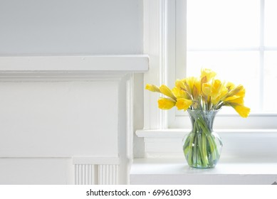 Yellow Daffodil flowers in glass vase on white fireplace mantle
