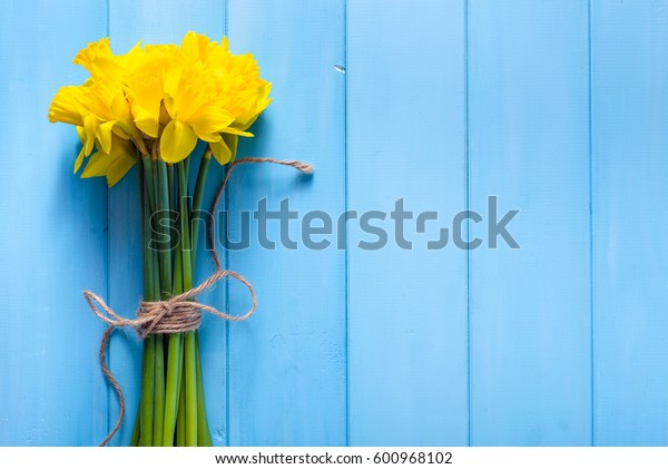 Yellow daffodils bouquet on wooden background, easter card