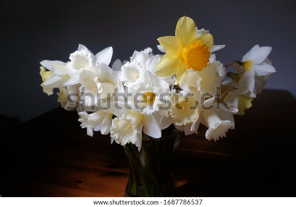 yellow daffodils are in a flower vase on the table