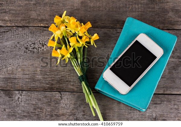 Yellow daffodils, notebook and mobile phone on the table.