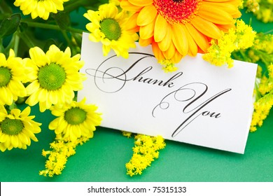 yellow daisy,gerbera and card signed thank you on green background