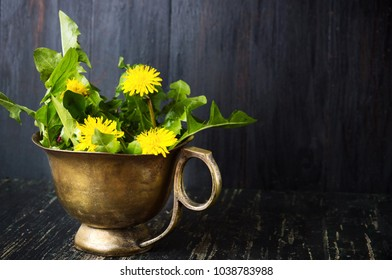 Yellow dandelion flowers in a vintage copper cup