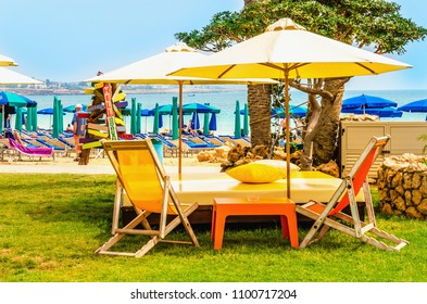 Yellow deck chairs under a yellow umbrella in the garden of a luxury hotel on the Mediterranean Sea, Cyprus